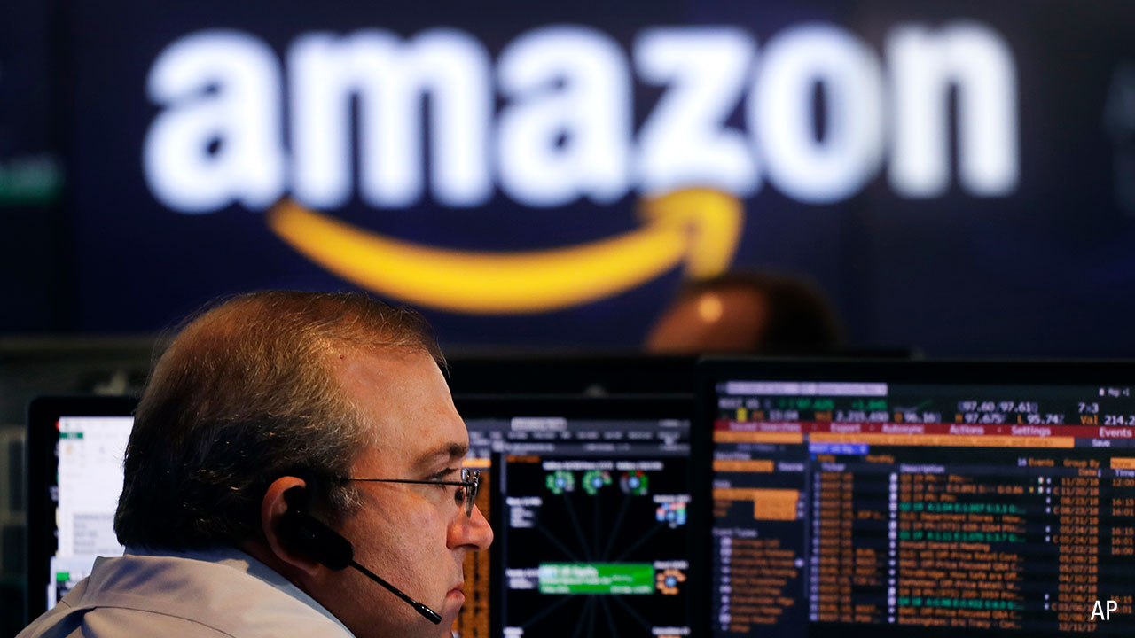A Nasdaq trader looks at a monitor with an Amazon logo in the background