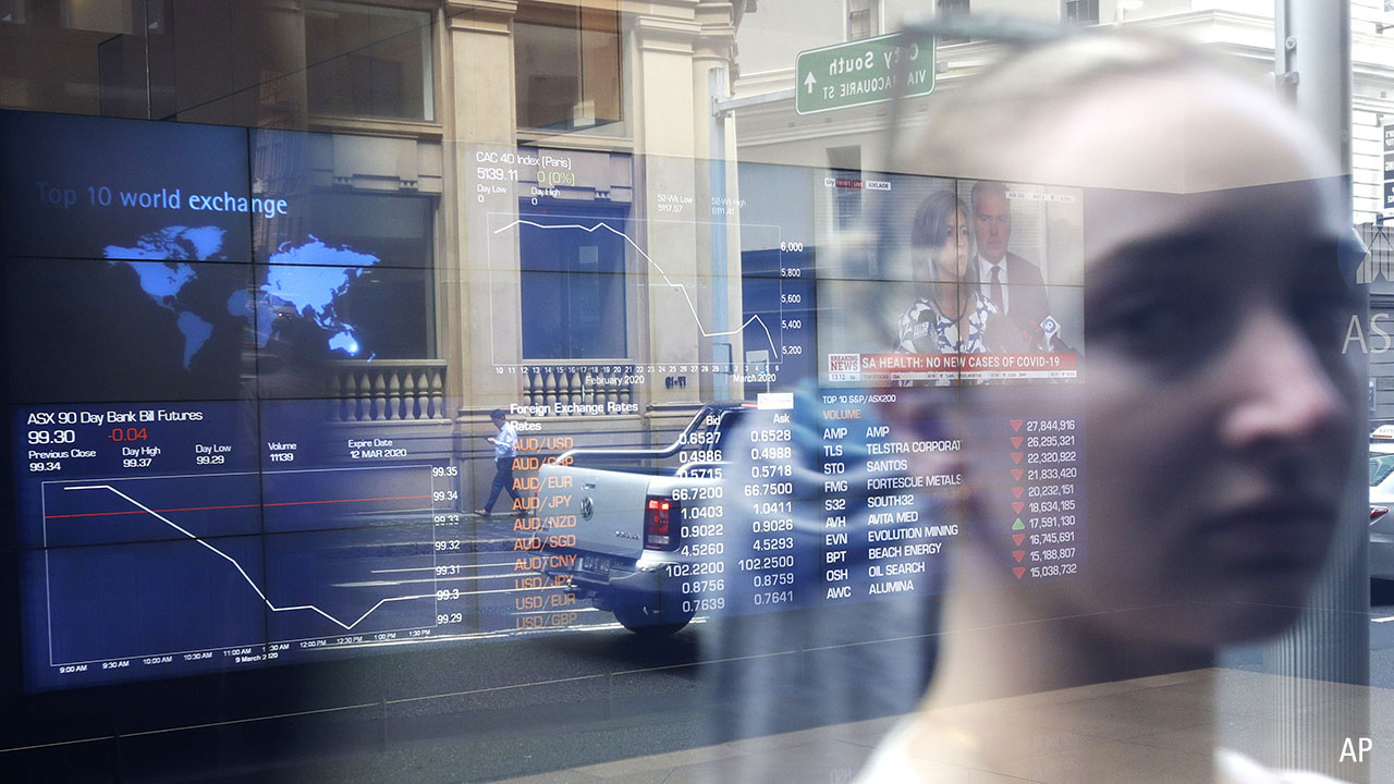 A photo showing the reflection of a woman looking at the ASX board