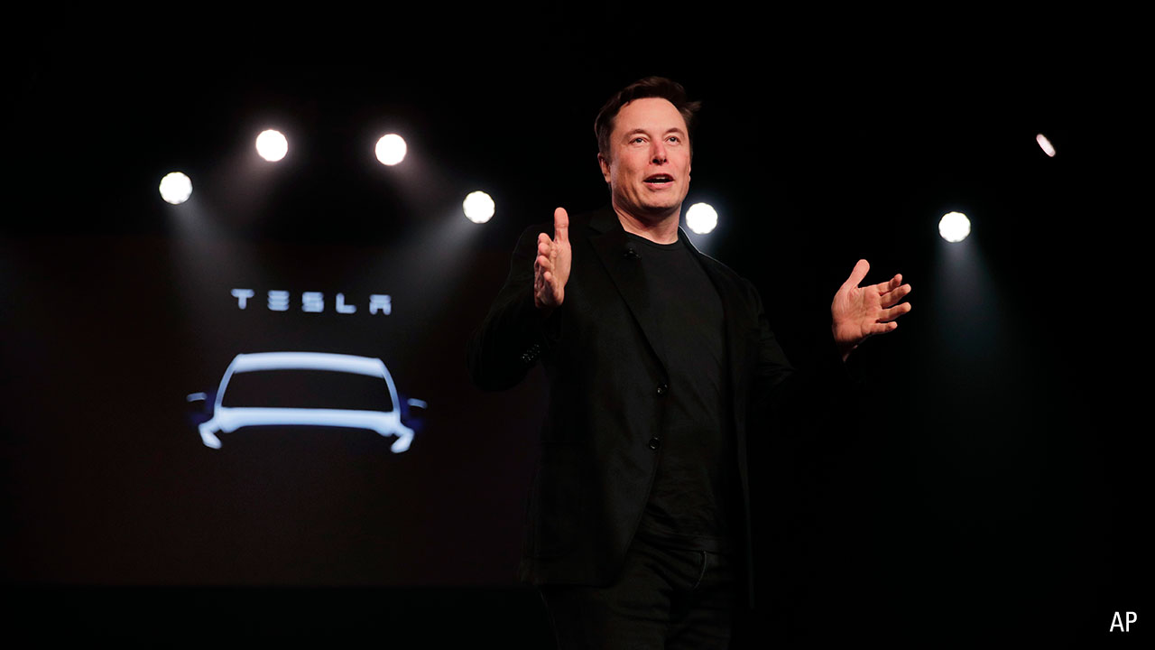 a picture of Tesla founder Elon Musk on stage presenting