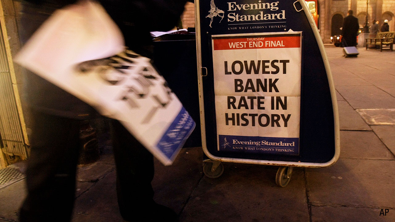 Thursday, Jan. 8, 2009, a newspaper vendor sells papers outside the Bank of England in the City of London