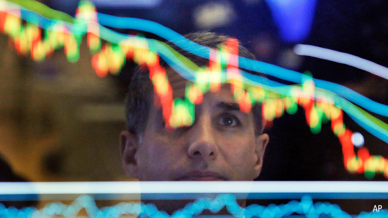 A man looking at the reflection of a share price graph