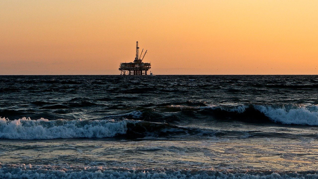 A picture of offshore rig seen from the shore at sunset