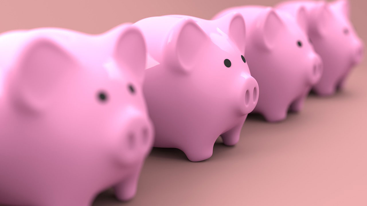 A picture of four pink piggy banks in a row