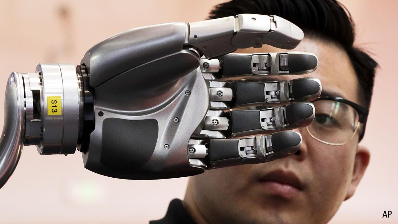 a man looks at a robotic hand