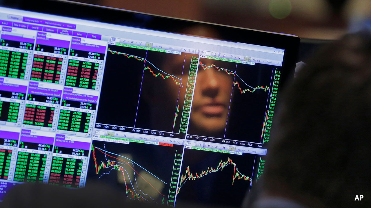 a trader reflected in a computer screening showing data movements