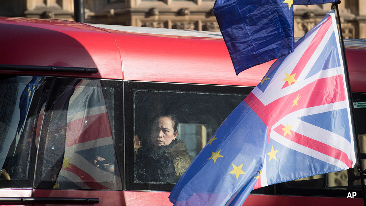 Passengers on a bus pass by an anti-Brexit demonstration in Westminster