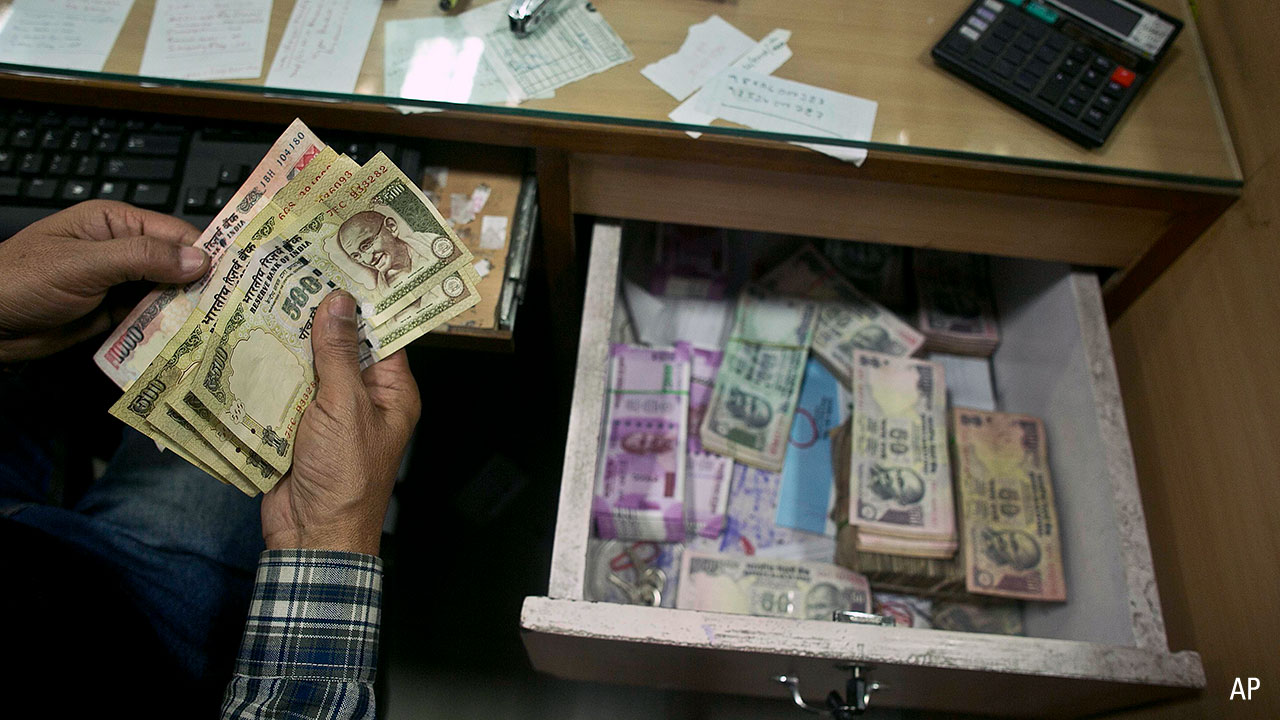 A bank official counts discontinued notes in a bank in Gauhati, India
